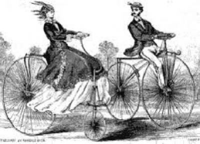 a man and a woman riding old fashioned bicycles
